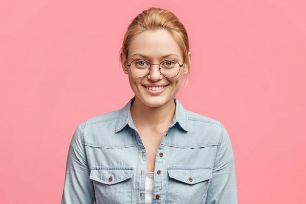 Portret van tevreden aantrekkelijke glimlachende vrouw gekleed in modieus spijkerjack, ziet iets aantrekkelijks in de winkel, geïsoleerd over roze studio