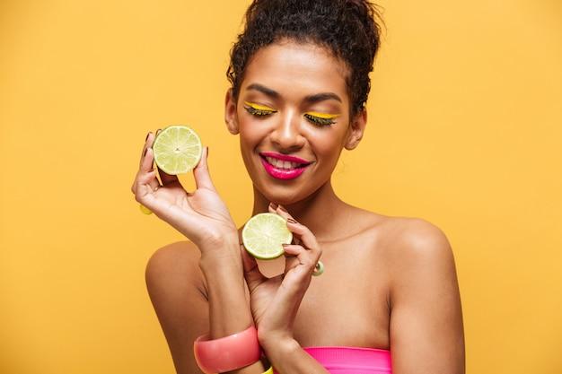 Portret van tevreden afro-amerikaanse vrouw die met trendy make-up de twee helften verse kalk in beide handen houden die, over gele muur worden geïsoleerd