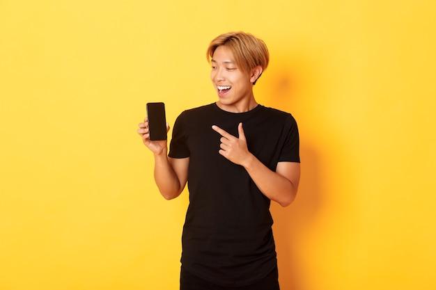 Portret van tevreden aziatische kerel die vinger richt en het smartphonescherm met tevreden glimlach bekijkt, toepassing toont, staande gele muur