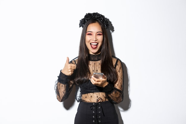 Portret van tevreden aziatische vrouw in elegante gotische jurk en zwarte krans met thumbs-up tijdens het gebruik van mobiele telefoon, staande op een witte achtergrond.