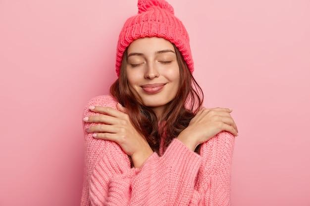 Portret van tevreden brunette vrouw knuffelt zichzelf, geniet van comfort in gebreide warme trui, houdt de ogen gesloten, koopt nieuwe winteroutfit, geïsoleerd op roze achtergrond.