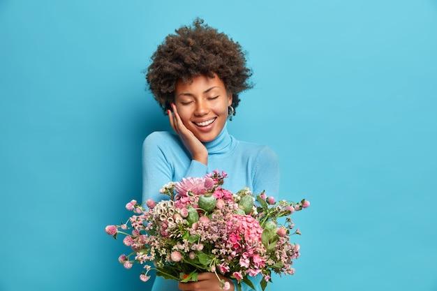 Portret van tevreden gekrulde jonge vrouw sluit ogen van plezier raakt wang zachtjes glimlacht teder blij om bloemen geïsoleerd over blauwe muur te krijgen