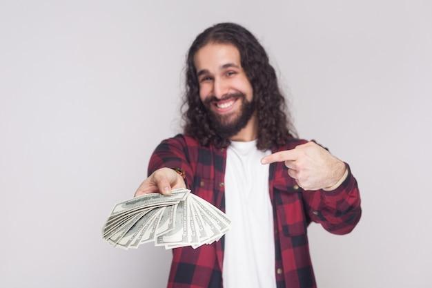 Portret van tevreden gelukkige jonge zakenman in rood geruit overhemd en zwart lang krullend haar dat staat, geeft en wijst met een vingerfan van geld. indoor studio-opname, geïsoleerd op een grijze achtergrond