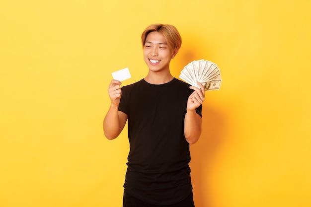 Portret van tevreden glimlachende, knappe aziatische kerel die tevreden naar creditcard kijkt terwijl hij ook geld vasthoudt, staande gele muur