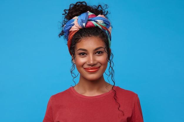 Portret van tevreden jonge mooie donkerharige krullende vrouw met verzameld haar die positief naar voorzijde kijkt met charmante glimlach, geïsoleerd over blauwe muur