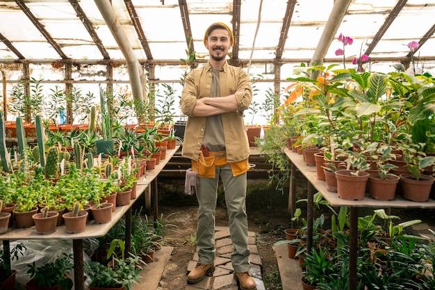 Portret van tevreden knappe jonge broeikasarbeider met gereedschapsriem permanent met gekruiste armen tussen tafels met planten in kas