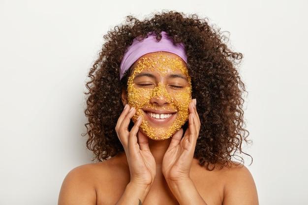 Portret van tevreden krullende dame gebruikt natuurlijke exfoliant om de huid te verzachten en de hydratatie te herstellen, past verzachtende zeezout gezichtsscrub toe, verwijdert bestaande schilfers, draagt een paarse hoofdband op het hoofd. zuiverheid