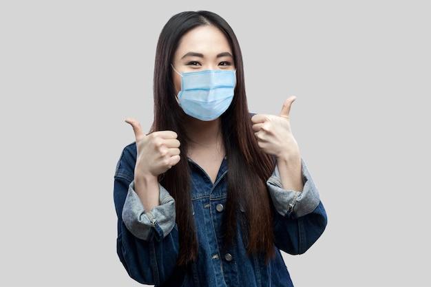 Portret van tevreden mooie aziatische jonge vrouw met chirurgisch medisch masker in blauwe jas staande, duimen omhoog, glimlachen en kijken naar de camera. studio opname, geïsoleerd op lichtgrijze achtergrond.