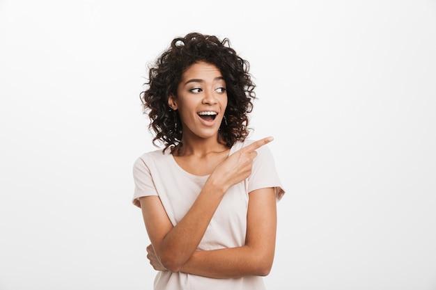 Portret van tevreden mooie vrouw in basist-shirt die opzij kijkt en wijsvinger op copyspace richt, dat over witte muur wordt geïsoleerd