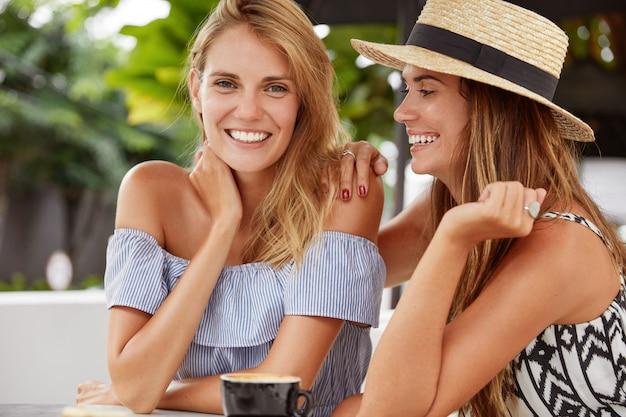 Portret van tevreden mooie vrouwtjes met een brede glimlach hebben samen een date, demonstreren homoseksuele relaties, poseren samen op het terras met een kopje koffie, geniet van een goede nachtrust tijdens het weekend