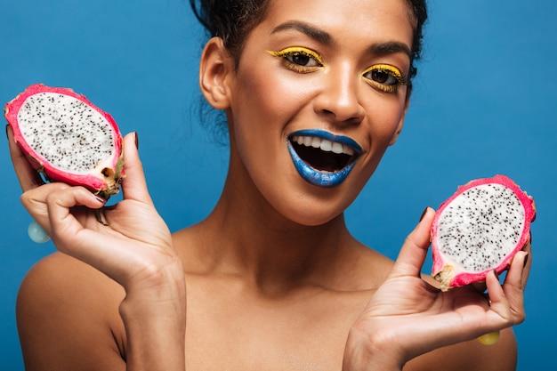 Portret van tevreden mulatvrouw die met heldere make-up van rijp pitayafruit genieten die in de helft over blauwe muur wordt gesneden