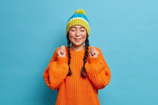 Portret van tevreden tienermeisje vormt met gesloten ogen glimlacht aangenaam houdt gebalde vuisten kan niet wachten tot er iets goeds gebeurt gekleed in winter gebreide trui en warme muts vormt binnen