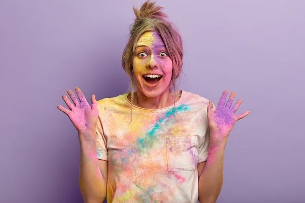 Portret van tevreden vrouw heeft gekleurd gezicht, toont handpalmen besmeurd met poeder, toont geluk en verbaasde reactie, poseert tegen paarse muur, viert traditionele indiase feestdag