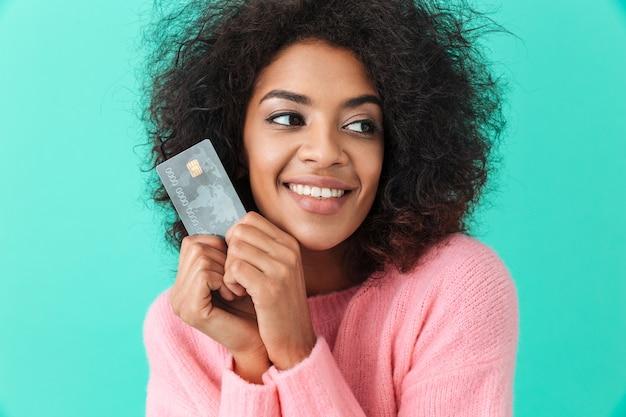 Portret van tevreden vrouw met ruwharig haar die plastic creditcard houden en van digitaal geld genieten, dat over blauwe muur wordt geïsoleerd
