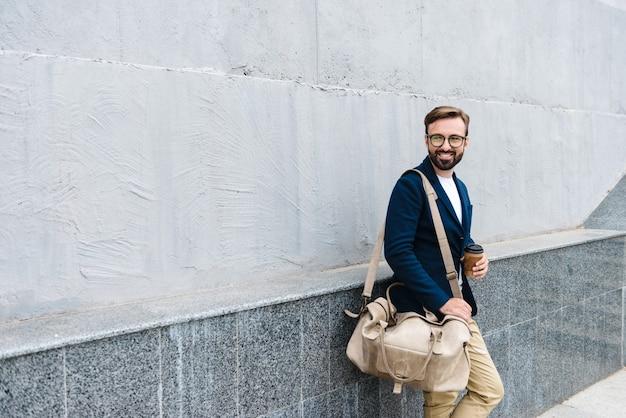 Portret van tevreden zakenman die een bril draagt die koffie drinkt uit een papieren beker en draagtas terwijl hij in de buurt van de muur staat