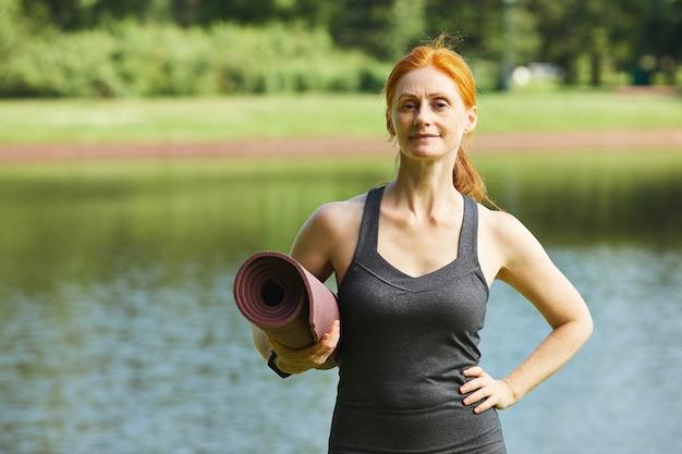 Portret van tevreden zelfverzekerde rijpe roodharige vrouw die zich tegen meer bevindt en yogamat houdt