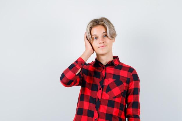 Portret van tiener blond mannetje dat oor bedekt met hand in casual shirt en peinzend vooraanzicht kijkt