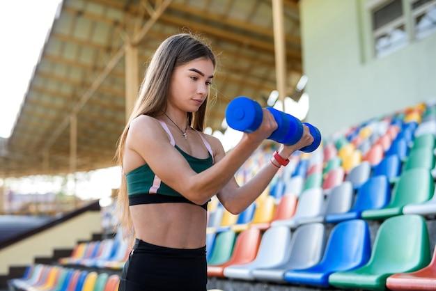 Portret van tiener fitness meisje doen oefening met halter in het stadion. .