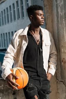 Portret van tiener het stellen met basketbalbal