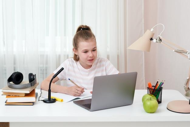 Portret van tiener online leren met hoofdtelefoons en laptop die nota's in een notitieboekjezitting nemen die bij haar bureau thuis huiswerk doen
