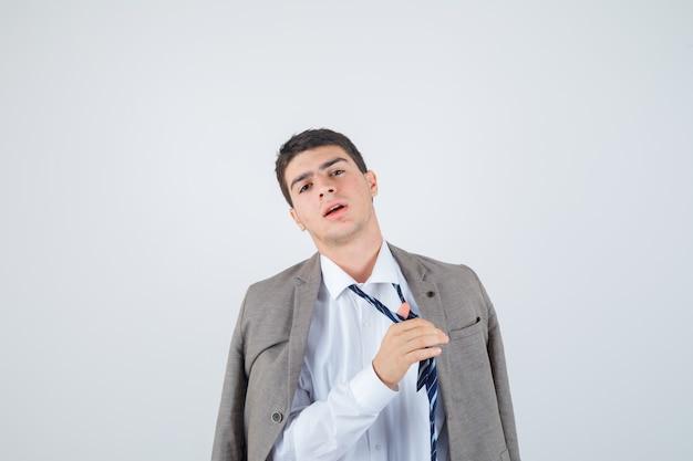 Portret van tienerjongen maakt stropdas los terwijl poseren in overhemd, jasje, gestreepte stropdas en op zoek naar vermoeid vooraanzicht
