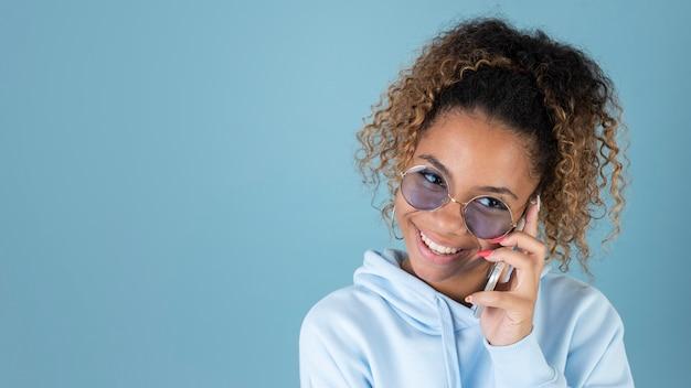 Portret van tienermeisje dat een zonnebril draagt en smartphone gebruikt
