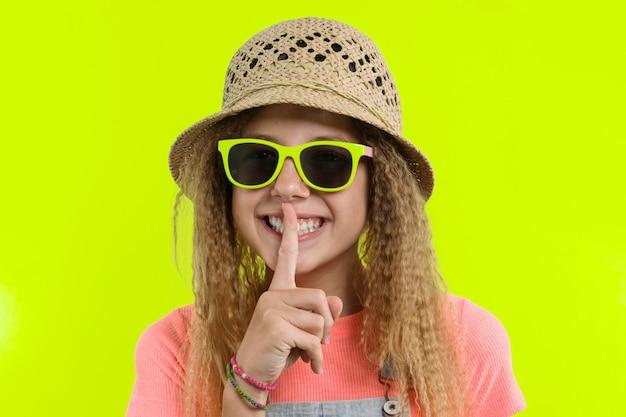 Portret van tienermeisje in zonnebril die stilteteken tonen