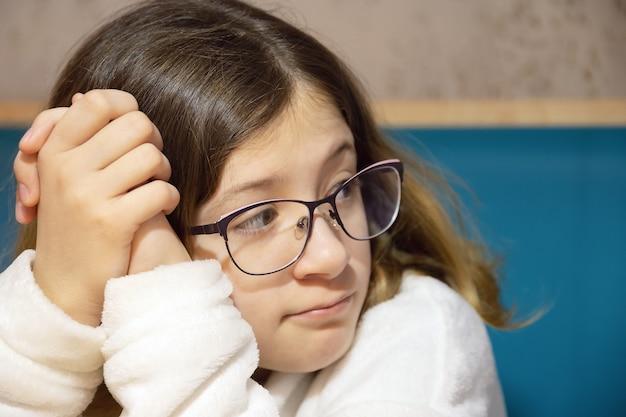 Portret van tienermeisje met bril en doordachte blik