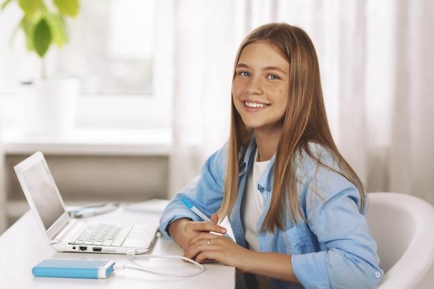 Portret van tienermeisje met koptelefoon zittend aan tafel lachend