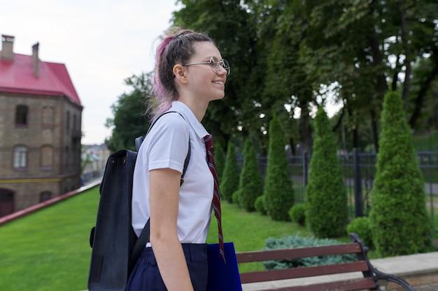Portret van tienermeisje met rugzak die naar school gaat, herfst zomerochtend, schoolgebouw achtergrond. terug naar school, terug naar de universiteit
