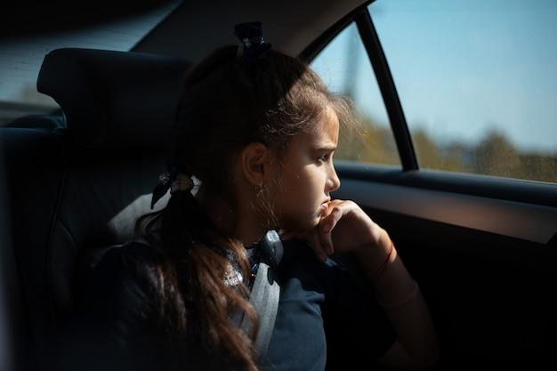 Portret van tienermeisje op de achterbank van de auto, kijkend naar het raam.