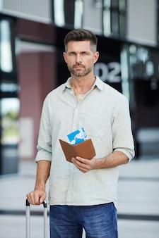 Portret van toerist die met bagage en kaartjes status op de luchthaven kijken