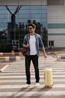 Portret van toerist met bruine rugzak en gele koffer