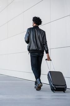 Portret van toeristische man met koffer tijdens het buiten lopen op straat. toerisme concept.
