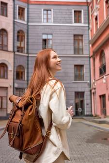 Portret van toeristische roodharige vrouw die foto's maakt van architectuur op retro filmcamera die op straat staat...