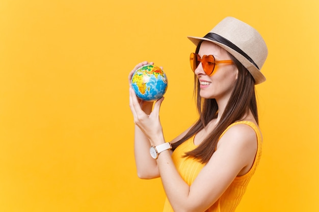 Portret van toeristische vrouw in zomerhoed, oranje bril houdt in handen globe geïsoleerd op gele achtergrond. reizen naar het buitenland om weekendjes weg te reizen. lucht vlucht reis concept. stop natuurafval.