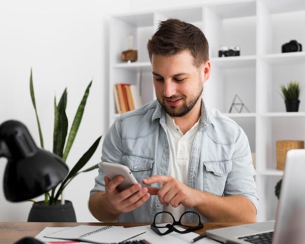 Portret van toevallige mannelijke die mobiele telefoon doorbladeren