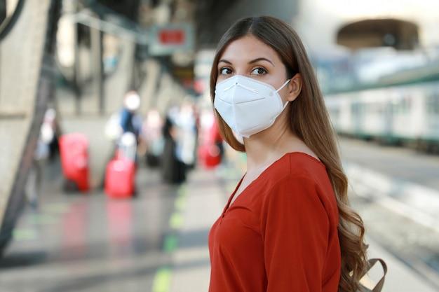 Portret van toevallige vrouwenwachtende trein met beschermend masker kn95 ffp2 bij treinstation