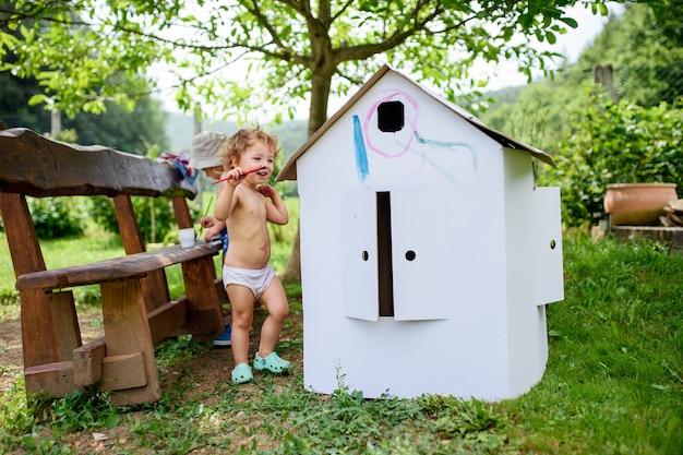 Portret van topless kleine blonde jongen en meisje die in de zomer buiten schilderen.