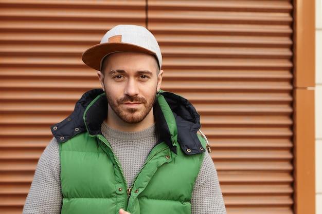 Portret van trendy aantrekkelijke jonge ongeschoren europese man in groen vest en snapback poseren op bruine haspel buitenshuis, wachtend op zijn date, nerveuze gelaatsuitdrukking hebben bezorgd