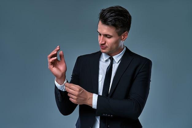 Portret van trendy, aantrekkelijke, verbluffende man in zwarte smoking met stropdas vast knop op manchetten van zijn witte overhemd, geïsoleerd op een grijze achtergrond.