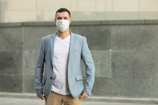 Portret van trendy man met een beschermend masker, wandelen in de stad