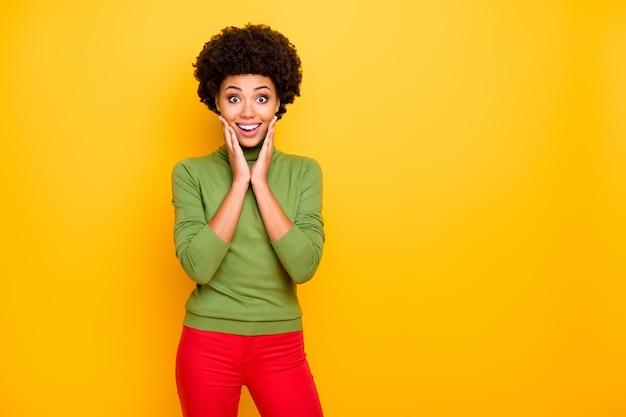 Portret van trendy stijlvolle vrolijke charmante meisjesachtige jongere in rode broeken aanraken wangen toothily glimlachen.