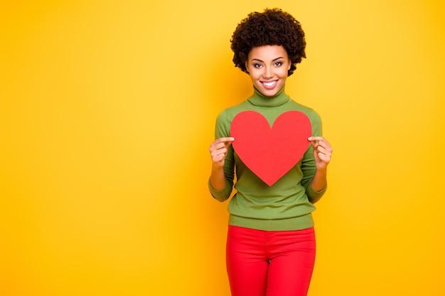 Portret van trendy stijlvolle vrolijke positieve schattige vrij lieve vrouw die lacht toothily groot rood hart in broek demonstreren.