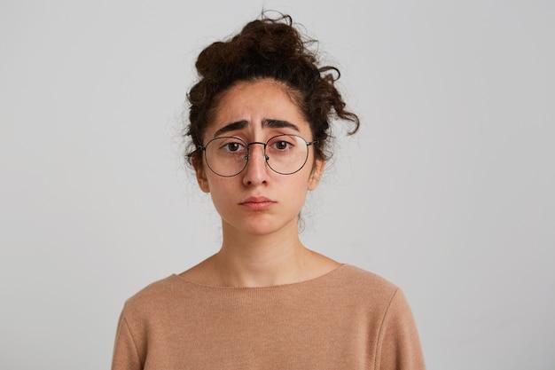Portret van triest boos georgische jonge vrouw met krullend haar draagt beige trui en bril voelt zich ongelukkig en gefrustreerd geïsoleerd over witte muur