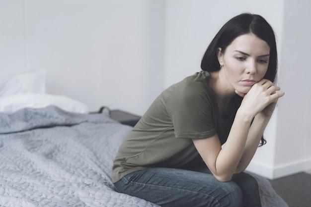 Portret van triest donkerharige vrouw zit op bed