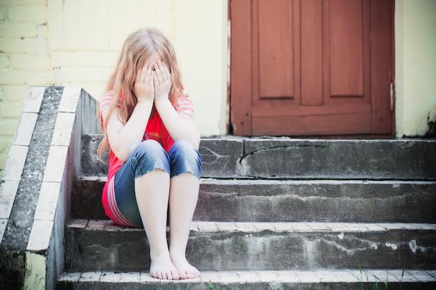 Portret van triest meisje zit in de buurt van muur