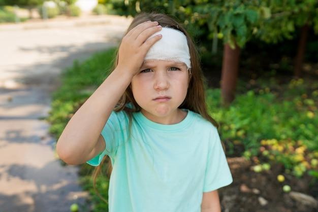 Portret van triest peuter meisje met verbonden hoofd buiten na een val