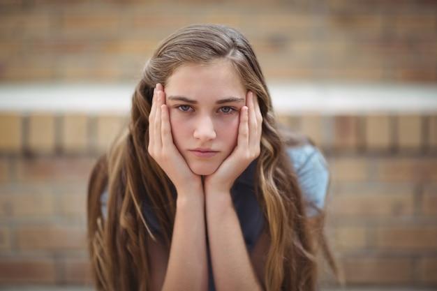 Portret van triest schoolmeisje zit alleen op de campus