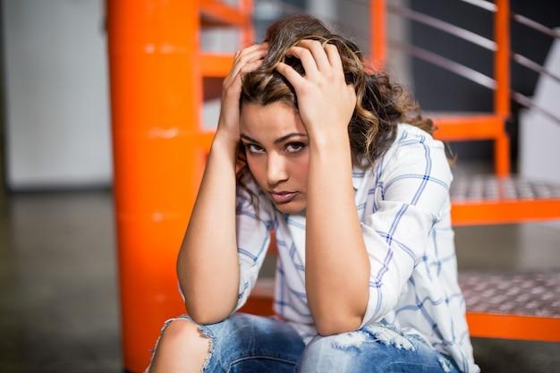 Portret van triest vrouwelijke executive zittend op trap